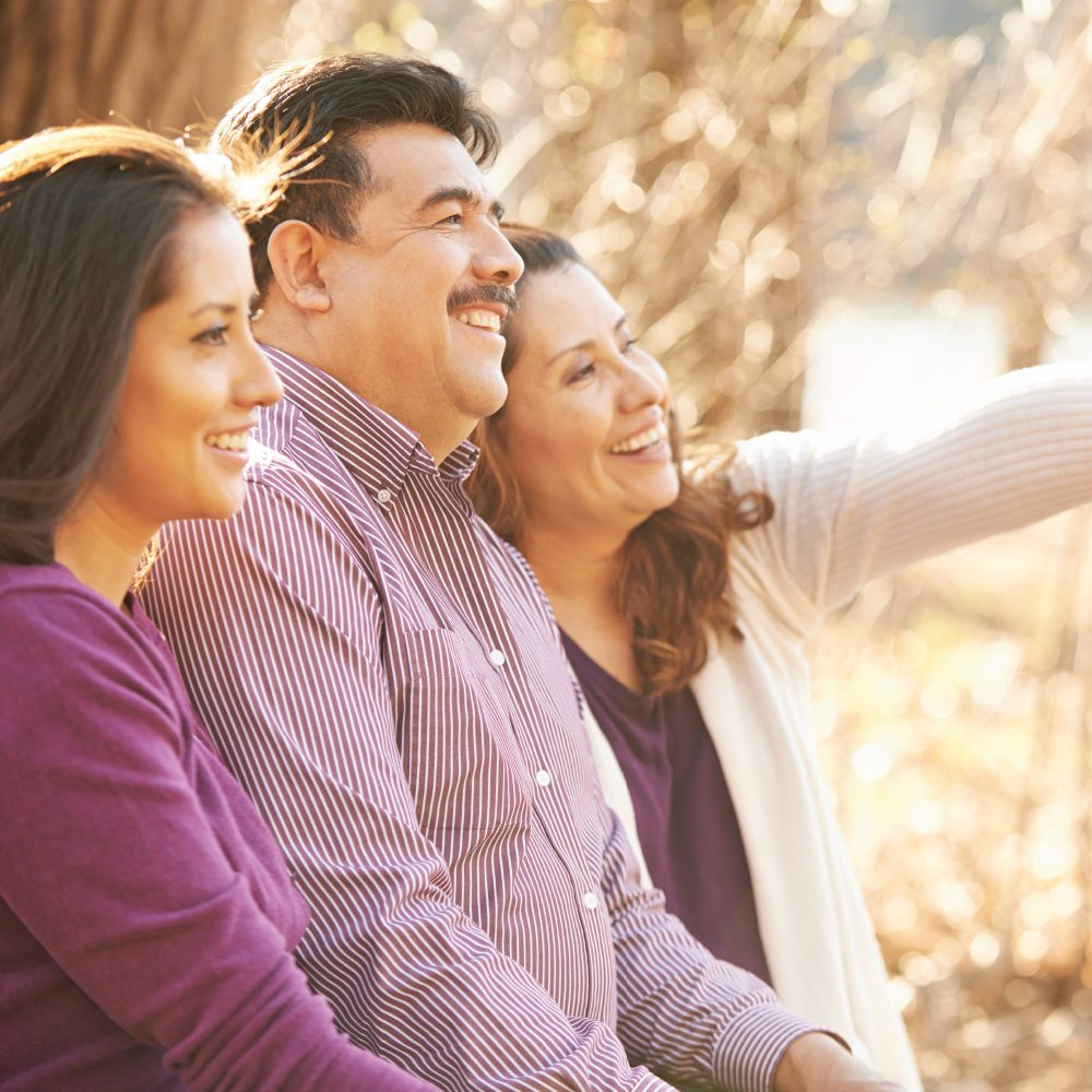 An Hispanic man with his wife and daughter smiling together outside